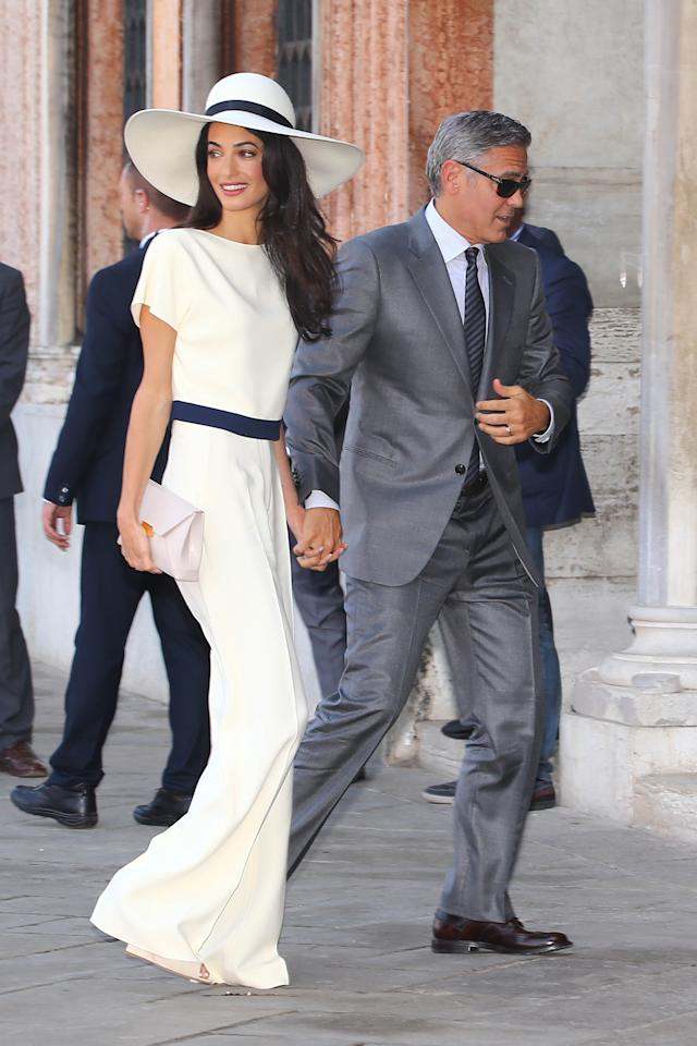 <p>Always the picture of glamour, Amal chose a cream jumpsuit and hat by Stella McCartney for her civil ceremony to officialize her marriage to George Clooney in 2014. </p>