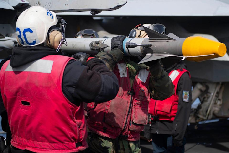 Sailors load missile on fighter jet on USS Theodore Roosevelt aircraft carrier