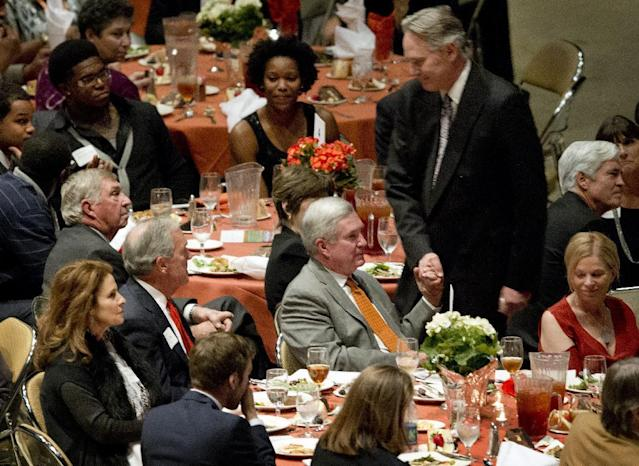 Texas head coach Mack Brown, seated in gray suit, shakes hands with the new Texas Athletic Director Steve Patterson at the University of Texas Longhorns Honors banquet at the Frank Erwin Center on Friday Dec. 13, 2013. At left is outgioing UT Athletic Director DeLoss Dodds. (AP Photo/Austin American-Statesman, Jay Janner)