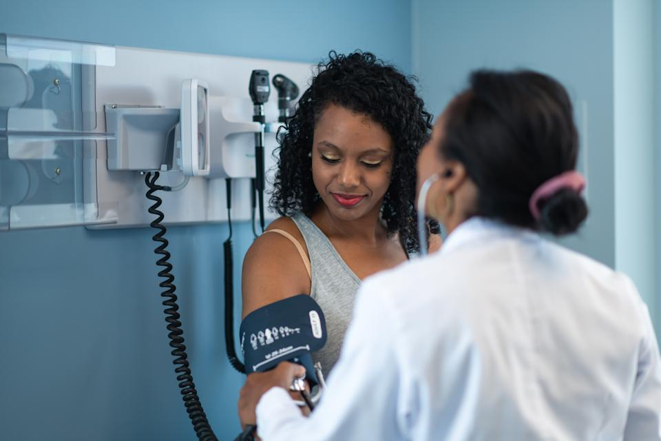 A young black woman is at a routine medical appointment. Her healthcare provider is an ethnic woman. The patient is sitting on an examination table in a clinic. The doctor is checking the patient's blood pressure. The patient is smiling while looking down at her arm.