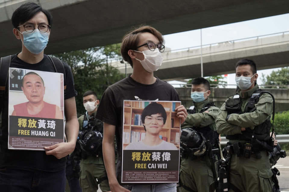 Pro-democracy activists holding picture of detained Chinese human rights activists, protest outside the Chinese liaison office in Hong Kong, Thursday, Oct. 1, 2020 on the occasion of China's National Day. They demanded to release the 12 Hong Kong activists detained at sea by Chinese authorities. (AP Photo/Kin Cheung)