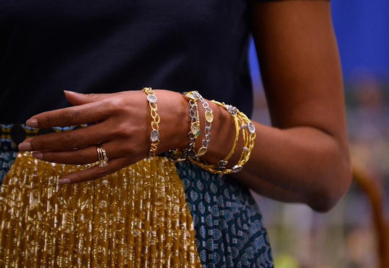 The jewelery worn by US First Lady Michelle Obama is pictured as she speaks during a book signing event of her book 'American Grown: The Story of the White House Kitchen Garden and Gardens Across America,' at Politics & Prose in Washington, DC, on May 7, 2013. Photo credit: JEWEL SAMAD/AFP/Getty Images