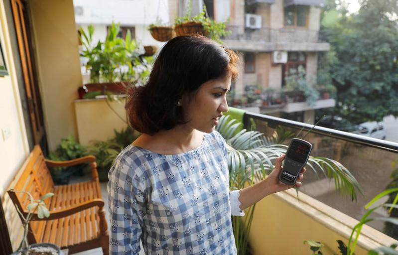 Nabeela Moinuddin uses an air quality monitor device to check the pollution level in her house in New Delhi
