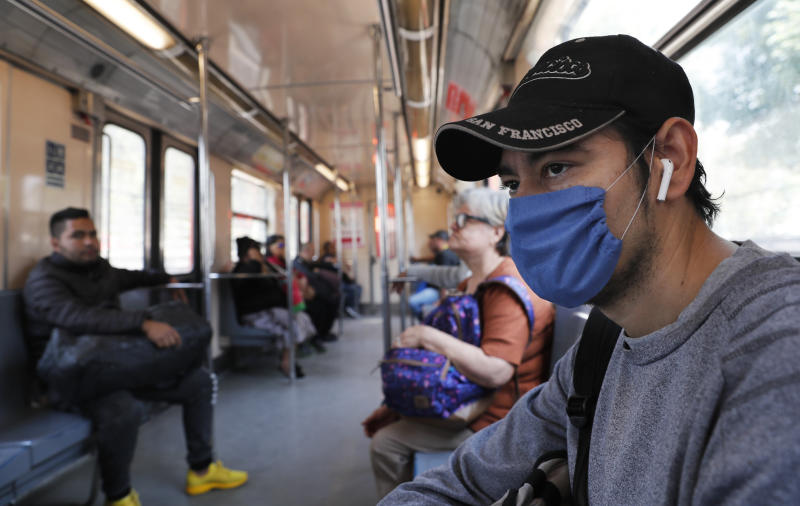 A man wears a protective mask as a precaution against the spread of the new coronavirus in the metro in Mexico City, Friday, Feb. 28, 2020. Mexico's assistant health secretary announced Friday that the country now has confirmed cases of the COVID-19 virus. (AP Photo/Marco Ugarte)