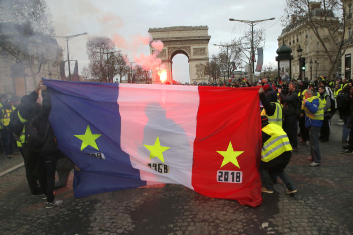 """Protesters known as the """"yellow vests"""" display their national flag as they march on the Paris' famed Champs-Elysees Avenue, France, Saturday, Dec. 8, 2018. (Photo: Michel Euler/AP)"""