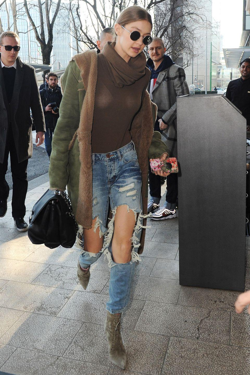<p>In a brown cowl neck top, olive green shearling coat, ripped jeans, lace-up ankle boots, rounded sunglasses and black leather handbag while out in Milan</p>