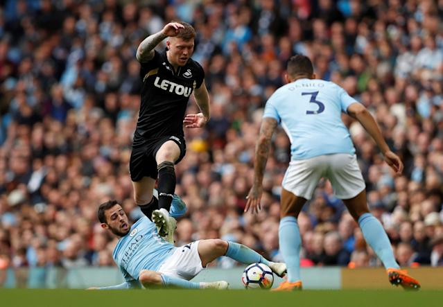 "Soccer Football - Premier League - Manchester City v Swansea City - Etihad Stadium, Manchester, Britain - April 22, 2018 Manchester City's Danilo and Bernardo Silva in action with Swansea City's Alfie Mawson Action Images via Reuters/Lee Smith EDITORIAL USE ONLY. No use with unauthorized audio, video, data, fixture lists, club/league logos or ""live"" services. Online in-match use limited to 75 images, no video emulation. No use in betting, games or single club/league/player publications. Please contact your account representative for further details."
