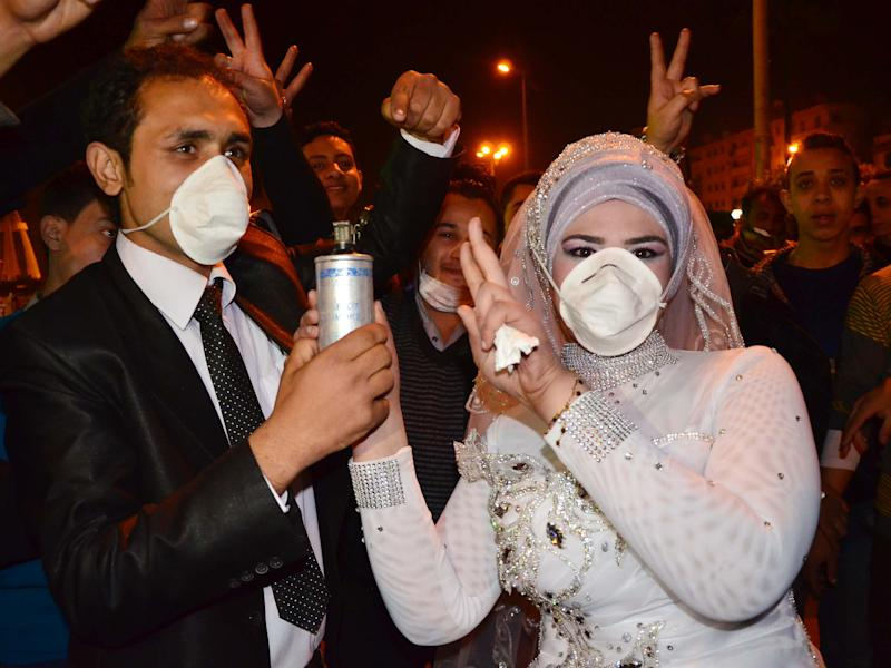 In this Monday, March 4, 2013 photo, revolutionary activist, Mohammed Magdy and his bride, wearing masks against tear gas and jointly holding a used tear gas container, celebrate their wedding in Revolution Square, the center of weeks of anti-government clashes, in the Nile Delta city of Mansoura, Egypt. Protesters in Mansoura, and other Egyptian cities have been calling for civil disobedience campaigns, or work stoppages, to bring down President Mohammed Morsi who they accuse along with the Muslim Brotherhood of trying to monopolize power and of reneging on promises of reform. (AP Photo)