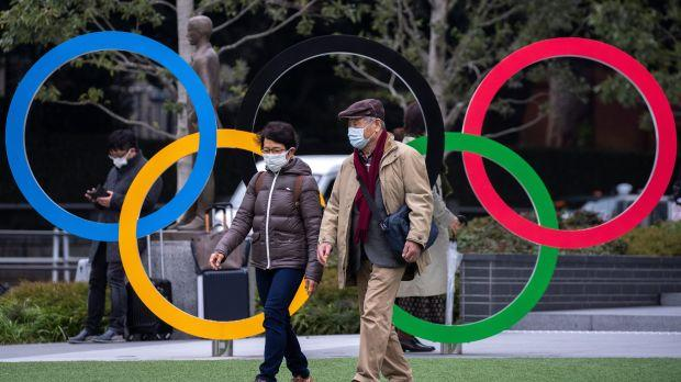 People wearing protective face masks are seen next to the Olympic rings