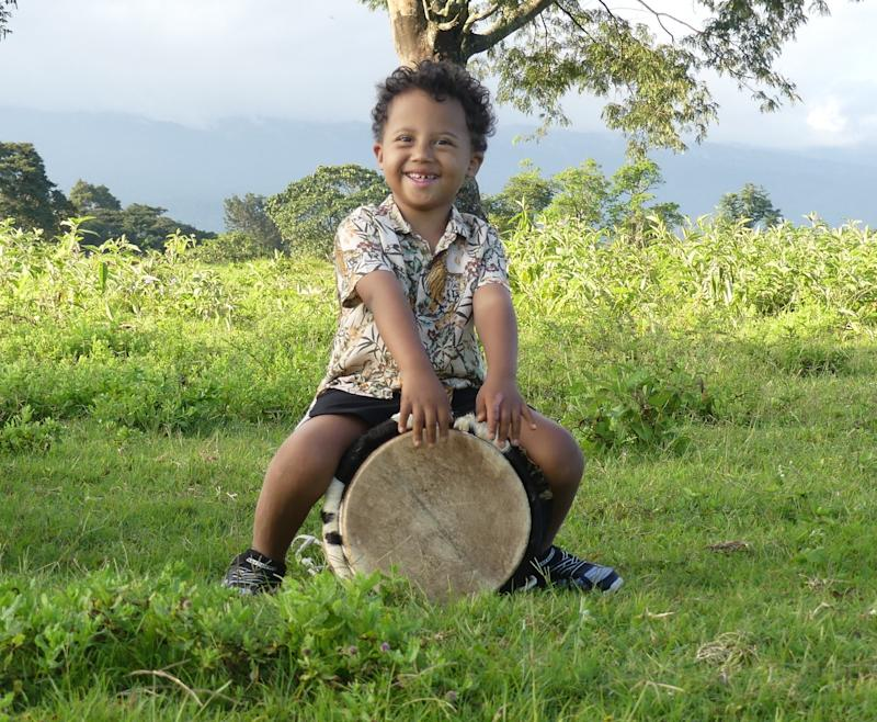 Hayley's son who has Down syndrome sitting on a drum outside.