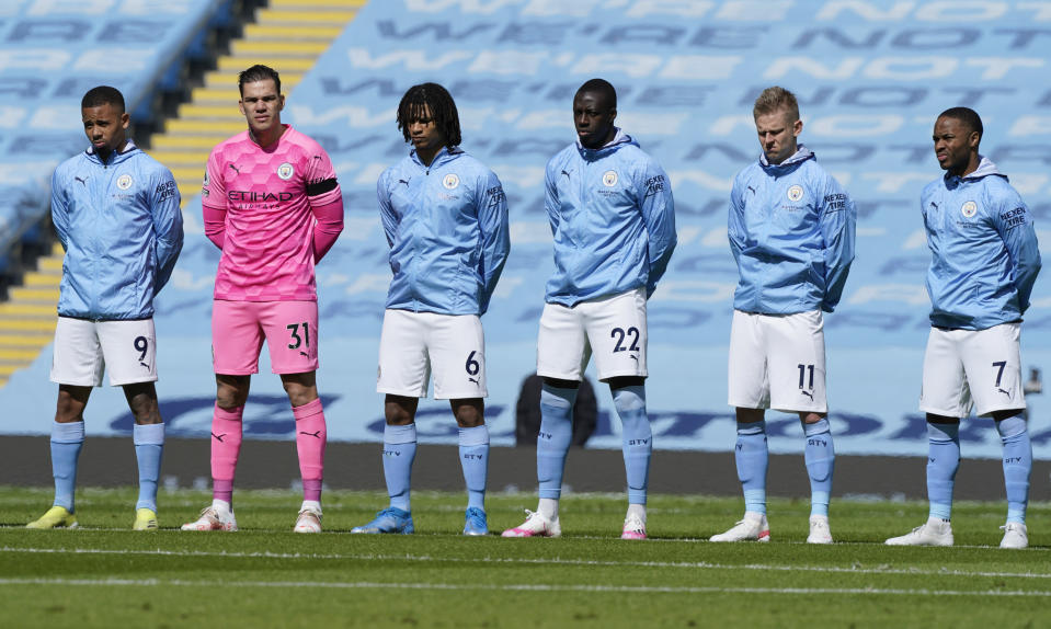 Manchester City players stand for a two minute silence prior to kick off to mark the passing of Prince Philip at the English Premier League soccer match between Manchester City and Leeds United at Etihad Stadium, Manchester, England, Saturday April 10, 2021. (AP Photo/Tim Keeton,Pool)