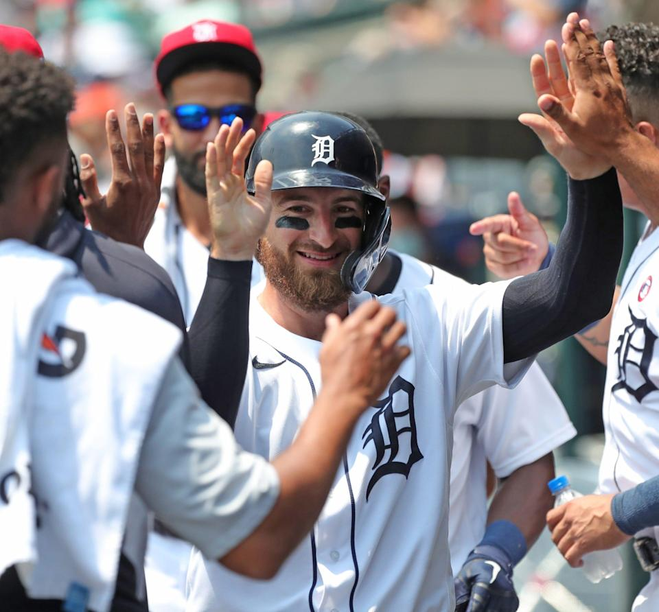 Detroit Tigers catcher Eric Haase high-fives teammates after scoring during the second inning against the Chicago White Sox at Comerica Park in Detroit, Sunday, July 4, 2021.