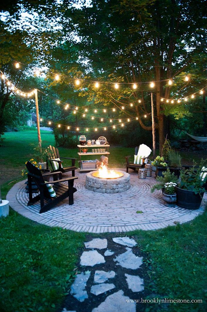 """<p>There's nothing better than sitting around a fire pit with friends and family, drinking, reminiscing, and making s'mores. Only string lights could make this moment even cozier.</p><p><strong>See more at <a href=""""http://www.brooklynlimestone.com/2016/08/country-cottage-diy-circular-firepit.html"""" rel=""""nofollow noopener"""" target=""""_blank"""" data-ylk=""""slk:Brooklyn Limestone"""" class=""""link rapid-noclick-resp"""">Brooklyn Limestone</a>.</strong></p><p><a class=""""link rapid-noclick-resp"""" href=""""https://www.amazon.com/dp/B07T3JX7VM/ref=sspa_dk_detail_3?tag=syn-yahoo-20&ascsubtag=%5Bartid%7C10050.g.3404%5Bsrc%7Cyahoo-us"""" rel=""""nofollow noopener"""" target=""""_blank"""" data-ylk=""""slk:Shop String Lights"""">Shop String Lights</a></p>"""