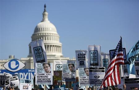 "Demonstrators hold up their signs during the ""Stop Watching Us: A Rally Against Mass Surveillance"" march near the U.S. Capitol in Washington, October 26, 2013. REUTERS/Jonathan Ernst"