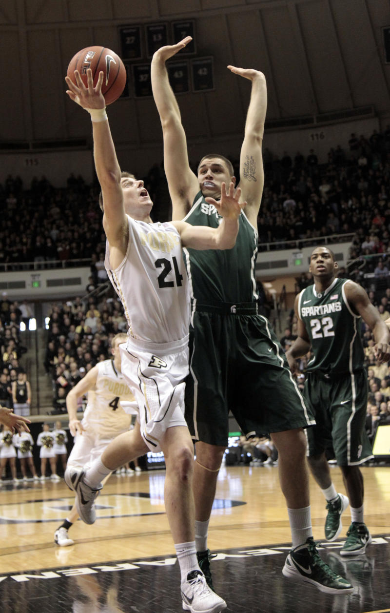 Purdue guard Ryne Smith, left, shoots in front of Michigan State forward Alex Gauna in the first half of an NCAA college basketball game in West Lafayette, Ind.  Sunday, Feb. 19, 2012. (AP Photo/AJ Mast)