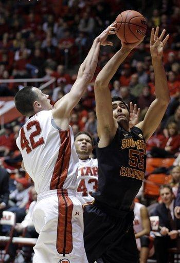 Utah center Jason Washburn (42) blocks the shot of Southern California center Omar Oraby (55), of Egypt, while Utah guard Cedric Martin (43) watches during the first half during an NCAA basketball game Saturday, Jan. 12, 2013, in Salt Lake City. (AP Photo/Rick Bowmer)