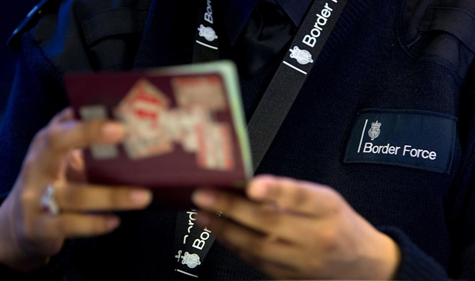 File photo dated 04/06/14 of a Border Force officer checking passports. An Australian style-points-based immigration system should be introduced into the UK by the end of the year, the Home Secretary will reportedly tell Cabinet.