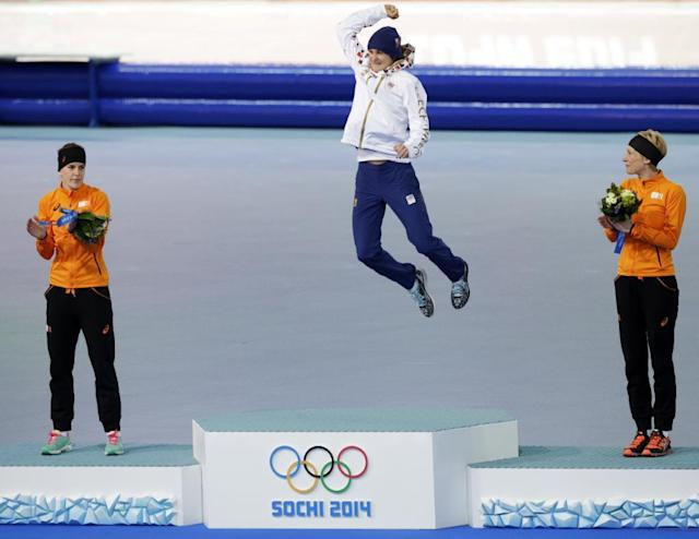 Silver medallist Ireen Wust of the Netherlands, left, and bronze medallist Carien Kleibeuker of the Netherlands, right, applaud gold medallist Martina Sablikova of the Czech Republic as she jumps for joy during the flower ceremony for the women's 5,000-meter speedskating race at the Adler Arena Skating Center during the 2014 Winter Olympics in Sochi, Russia, Wednesday, Feb. 19, 2014. (AP Photo/Matt Dunham)