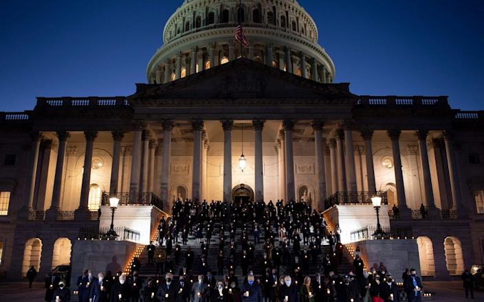 Lawmakers hold a moment of silence during a candelight ceremony on Capitol Hill in honor of the 500,000 people who lost their lives to Covid-19 - Brendan Smialowski/AFP