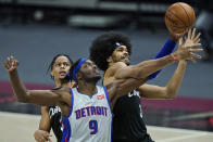 Detroit Pistons' Jerami Grant, left, and Cleveland Cavaliers' Jarrett Allen battle for a loose ball in the second half of an NBA basketball game, Wednesday, Jan. 27, 2021, in Cleveland. (AP Photo/Tony Dejak)