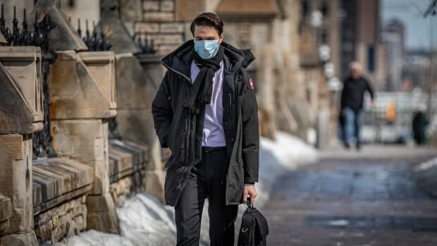 A person walks down Wellington Street near Parliament Hill on Wednesday, March 10, 2021. On Sunday, health official reported 68 new cases of COVID-19 in the nation's capital.  (Brian Morris/CBC - image credit)