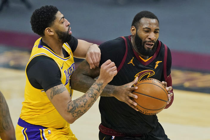 Cleveland Cavaliers' Andre Drummond, right, drives past Los Angeles Lakers' Anthony Davis in the first half of an NBA basketball game, Monday, Jan. 25, 2021, in Cleveland. (AP Photo/Tony Dejak)