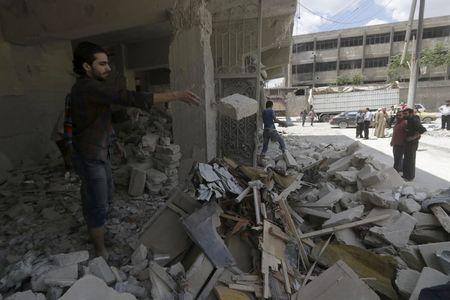 People remove rubble from a site hit by what activists said was a barrel bomb dropped by forces loyal to Syria's President Bashar al-Assad at al-Saleheen neighborhood of Aleppo May 14, 2015. REUTERS/Hosam Katan