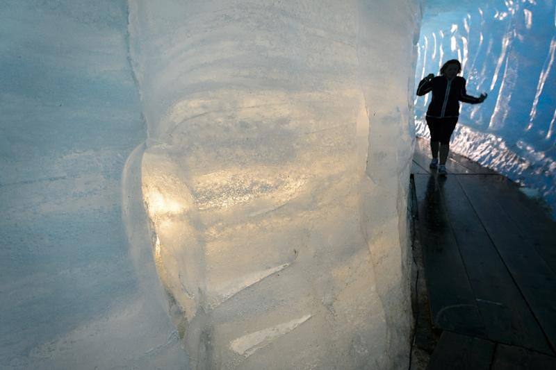A tourist visits an ice cave inside the Rhone Glacier, which has retreated about 40 metres in length due to melting in the past decade alone (AFP Photo/Fabrice Coffrini)