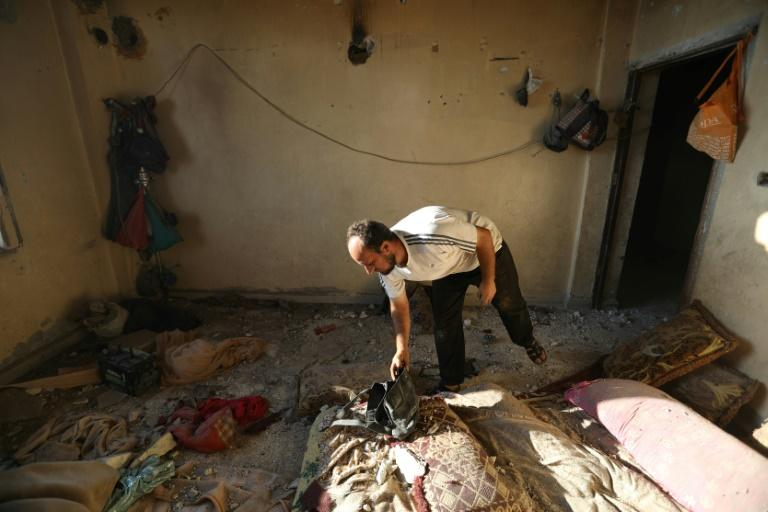 A man checks damage to a building housing displaced Syrians following an air strike in Idlib province