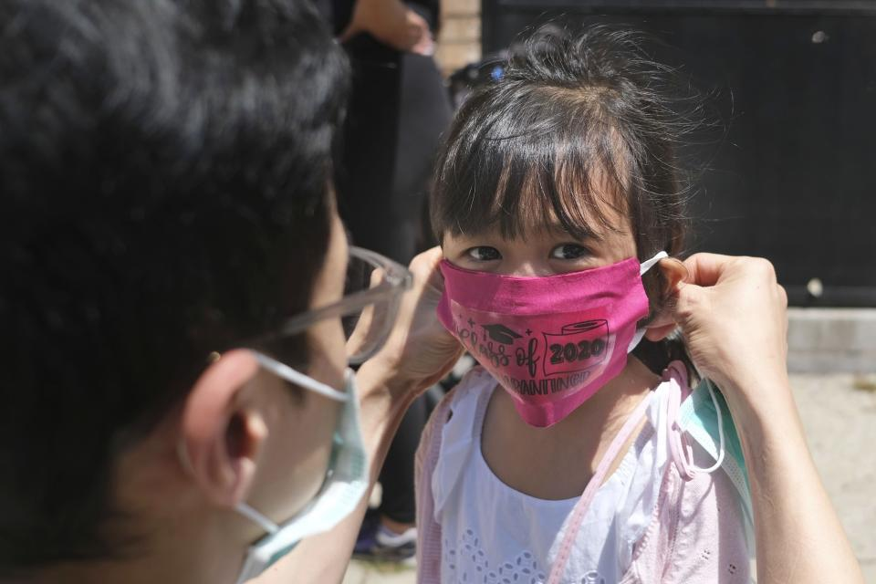 FILE - In this June 10, 2020, file photo, Olivia Chan's father helps her with a new mask she received during a graduation ceremony for her Pre-K class in front of Bradford School in Jersey City, N.J. As the Trump administration pushes full steam ahead to force schools to resume in-person education, public health experts warn that a one-size-fits-all reopening could drive infection and death rates even higher. (AP Photo/Seth Wenig, File)