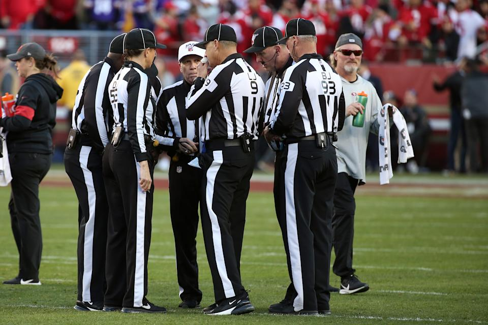 Officials huddle on the field during an NFL game.