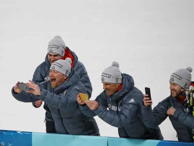 Nordic Combined Events - Pyeongchang 2018 Winter Olympics - Men's Individual 10 km Final - Alpensia Cross-Country Skiing Centre - Pyeongchang, South Korea - February 20, 2018 - Coaches of the German team take pictures during the victory ceremony. REUTERS/Dominic Ebenbichler