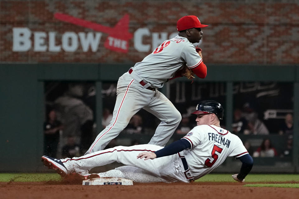 Philadelphia Phillies shortstop Didi Gregorius (18) avoids Atlanta Braves' Freddie Freeman (5) as he attempts to turn a double play on an Ozzie Albies ground ball in the eighth inning of a baseball game Tuesday, Sept. 28, 2021, in Atlanta. Albies was safe at first base. (AP Photo/John Bazemore)