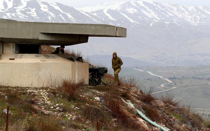 An Israeli soldier walks near a military post close to the Druze village of Majdal Shams in the Israeli-occupied Golan Heights on the Syrian border - REUTERS