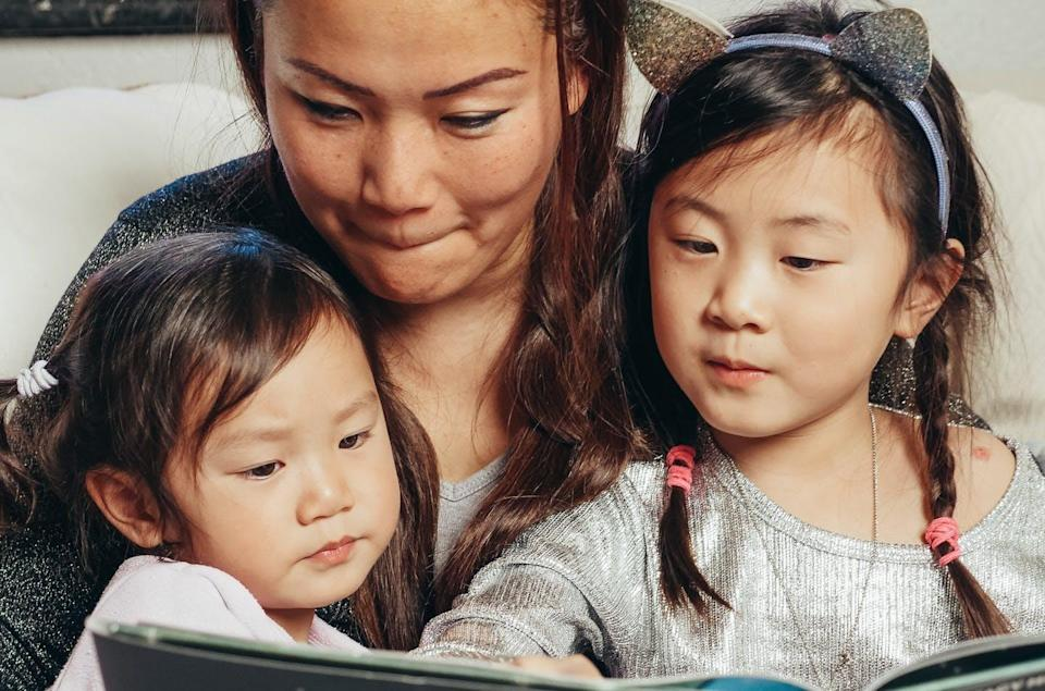 A mother reads to two daughters.