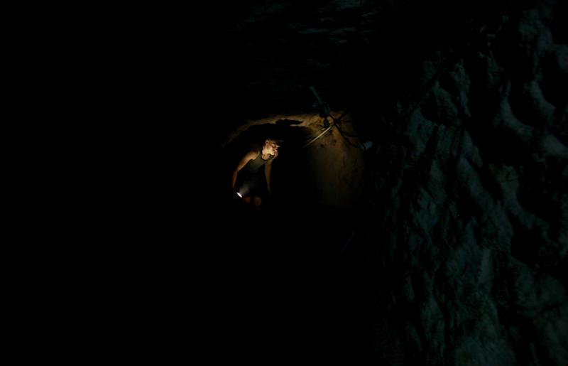 In this Monday, Sept. 30, 2013 photo, a Palestinian man works in a tunnel in Rafah, on the border between Egypt and the southern Gaza Strip. Since the summer, Egypt's military has tried to destroy or seal off most of the smuggling tunnels under the Gaza-Egypt border, a consequence of the heightened tensions between Cairo and the Hamas government in Gaza. The tunnels once employed thousands of young men in Gaza. By early September, with most tunnels closed, only few tunnel workers reported to their jobs for maintenance work. Some mask their faces with shirts to avoid identification while working, for fear of repercussions in case they were to travel to Egypt in the future. (AP Photo/Hatem Moussa)