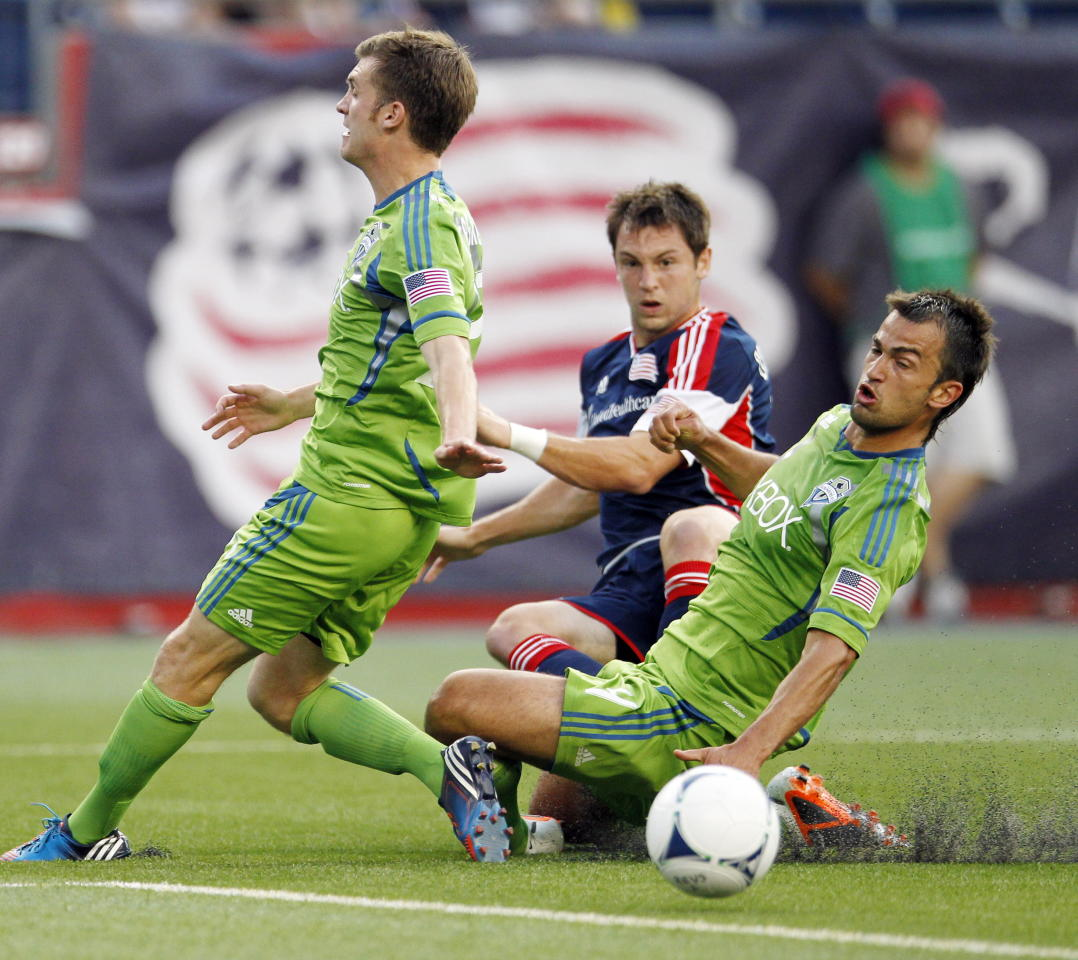 New England Revolution's Blake Brettschneider, center, watches his centering pass go between Seattle Sounders's Alex Caskey, left, and John Lozano, setting up a goal by Revolution's Saer Sene, in the first half of an MLS soccer game in Foxborough, Mass., Saturday, June 30, 2012. (AP Photo/Michael Dwyer)