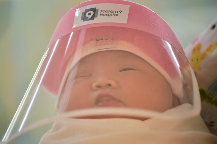 This photo taken through a glass window at a maternity ward shows a newborn baby wearing a face shield, in an effort to halt the spread of the COVID-19 coronavirus, at Praram 9 Hospital in Bangkok on April 9, 2020. (Photo by Lillian SUWANRUMPHA / AFP) (Photo by LILLIAN SUWANRUMPHA/AFP via Getty Images)