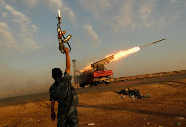 <p>A rebel fighter celebrates as his comrades fire a rocket barrage toward the positions of troops loyal to Libyan ruler Muammar Gaddafi April 14, 2011 west of Ajdabiyah, Libya. Rebels exchanged artillery and rocket fire with loyalist troops west of Ajdabiyah April 14 as the confict engulfing Libya continued. (Photo by Chris Hondros/Getty Images) </p>