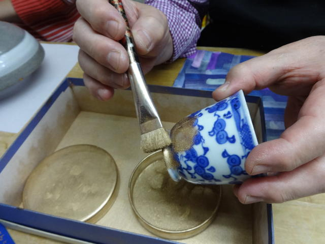 This Nov. 11, 2018 photo shows shows the final step of gold dust being brushed on to the repaired crack at the Kuge Crafts workshop in Tokyo. Kintsugi is an ancient Japanese method of repairing broken pottery with gold that creates a new work of art. (Linda Lombardi via AP)