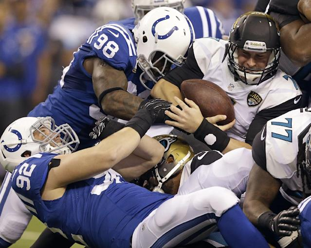 Jacksonville Jaguars' Chad Henne (7) is tackled by Indianapolis Colts' Robert Mathis (98) and Bjoern Werner (92) on a third down play during the first half of an NFL football game Sunday, Dec. 29, 2013, in Indianapolis. The Jaguars did not get the first down on the play. (AP Photo/Michael Conroy)