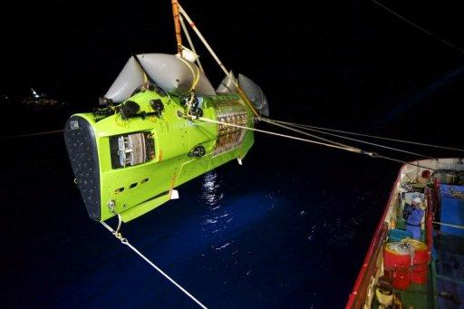 "The Deepsea Challenger submersible carrying filmmaker and National Geographic Explorer-in-Residence James Cameron is hoisted into the Pacific Ocean on Monday on its way to the ""Challenger Deep,"" the deepest part of the Mariana Trench. Cameron described a barren ""completely alien world"" on the ocean floor"