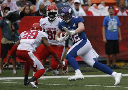 Minnesota Vikings tight end Kyle Rudolph (82) for the NFC runs the ball between Kansas City Chiefs strong safety Eric Berry (29) and Kansas City Chief outside linebacker Tamba Hali (91) during the second quarter the NFL Pro Bowl at Aloha Stadium in Honolulu, Hawaii January 27, 2013. REUTERS/Hugh Gentry