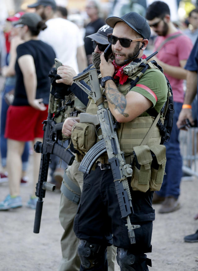 <p>Members of the John Brown Gun Club and Redneck Revolt protest outside the Phoenix Convention Center, Tuesday, Aug. 22, 2017, in Phoenix. Protests were held against President Trump as he hosted a rally inside the convention center. (AP Photo/Matt York) </p>