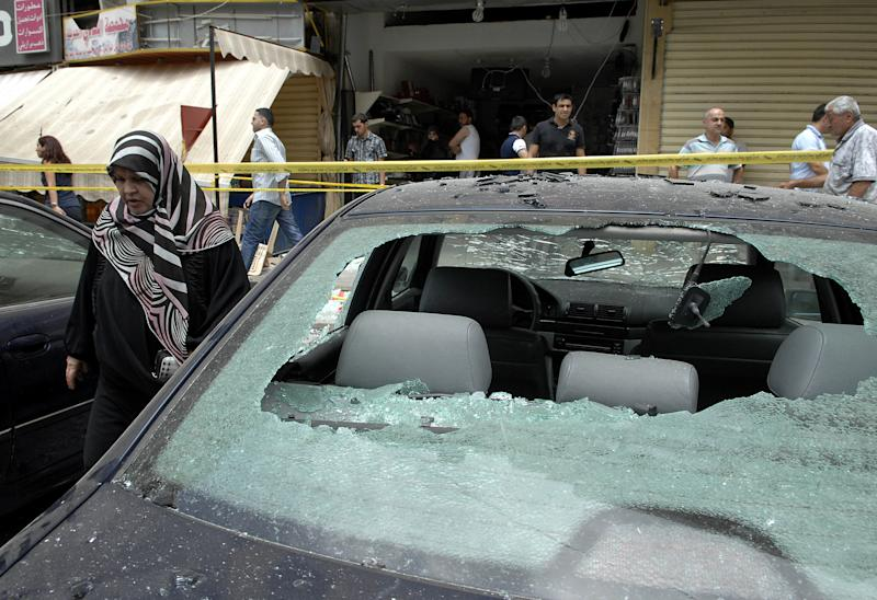 A woman walks past a car destroyed in a bombing in the Beir el-Abed, a southern suburb of Beirut, Lebanon, Tuesday, July 9, 2013. A large explosion rocked a stronghold of the Shiite militant Hezbollah group south of the Lebanese capital Tuesday, setting several cars on fire, sending a thick plume of black smoke billowing into the sky and wounding more than a dozen people, security officials said.(AP Photo/Ahmed Omar)