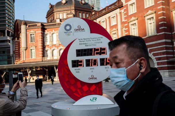 PHOTO: A man wearing a face mask amid concerns over the spread of the COVID-19 coronavirus walks past the Olympic countdown clock outside Tokyo station on March 23, 2020. (Behrouz Mehri/AFP via Getty Images)