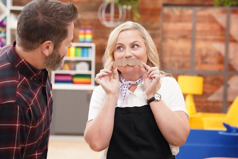 """Nick Offerman watches as his """"Making It"""" co-host Amy Poehler jokes around on set."""
