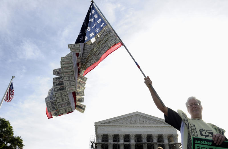 David Barrows of Washington holds a flag covered in money and corporate logos during a demonstration outside at the Supreme Court in Washington, Tuesday, Oct. 8, 2013, as the court heard arguments on campaign finance. The court is weighing a case that could open the way for more money to flow into US elections. The case being argued at the high court Tuesday is a test of its readiness to take its most aggressive swipe at campaign finance laws since a landmark 2010 decision lifted a cap on independent spending by corporations and labor unions. (AP Photo/Susan Walsh)