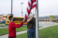 From left, 11th grader Ricardo Lopez, and 10th grader Justin Couch, raise the flag as a part of ROTC's flag detail outside at Ambridge Area Senior High School on the first day of Pennsylvania's mask mandate for K-12 schools and day care centers on Tuesday, Sept. 7, 2021, in Ambridge, Pa. (Andrew Rush /Pittsburgh Post-Gazette via AP)