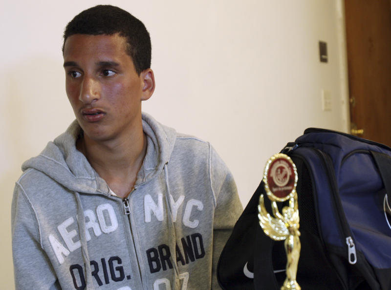 FILE - In this Thursday, April 18, 2013 file photo, Salah Eddin Barhoum, 17, sits in his apartment in Revere, Mass., with one of the trophies he won in an athletic competition, and the bag he was carrying on Monday near the finish line of the Boston Marathon. The high school student, of Moroccan descent, said he is scared to go outside after he was portrayed on the Internet and on the front page of the New York Post as connected to the deadly Boston Marathon bombings. Photos of Barhoum and a friend were posted on websites whose users have been scouring marathon finish line photos for suspects. (AP Photo/Rodrique Ngowi)